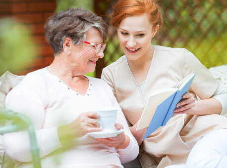 senior woman with female caregiver reading something on notebook