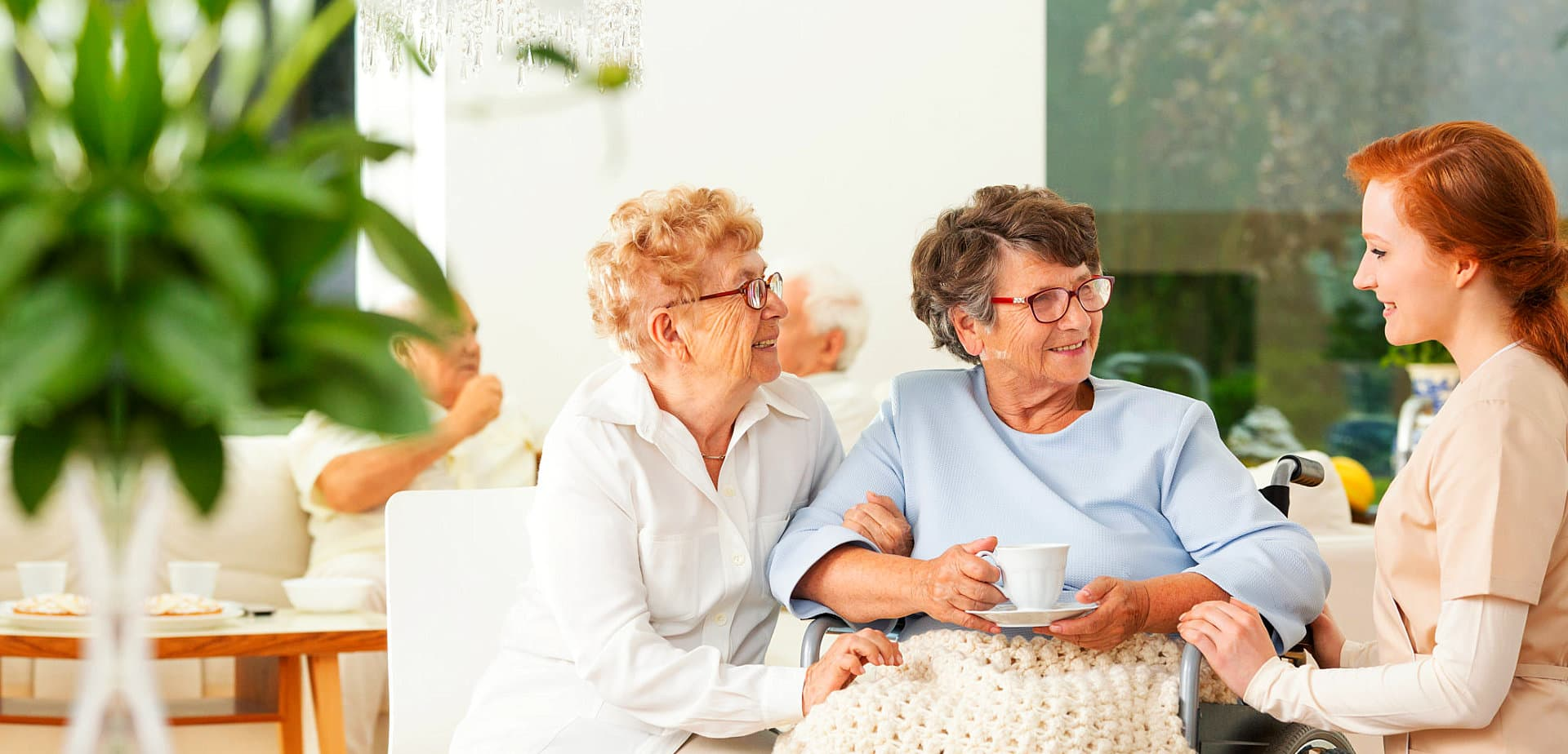 two senior women having conversation with female caregiver
