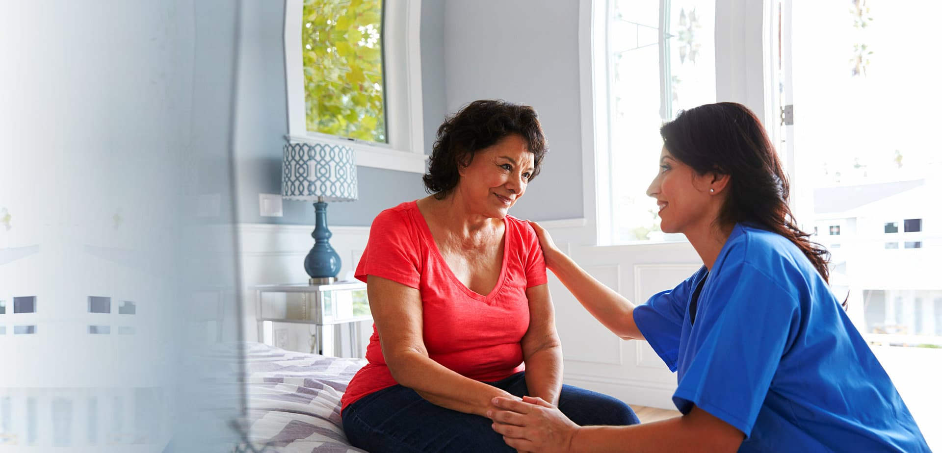 senior woman and female caregiver smiling at each other