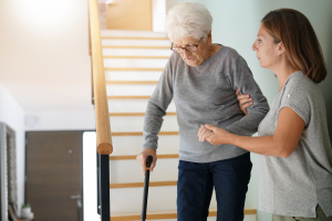 senior woman guided by caregiver at the stairs