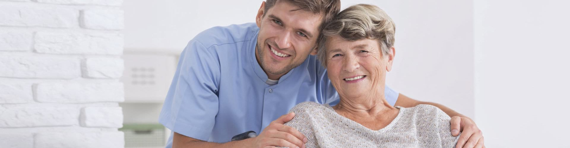 male caregiver with senior woman smiling